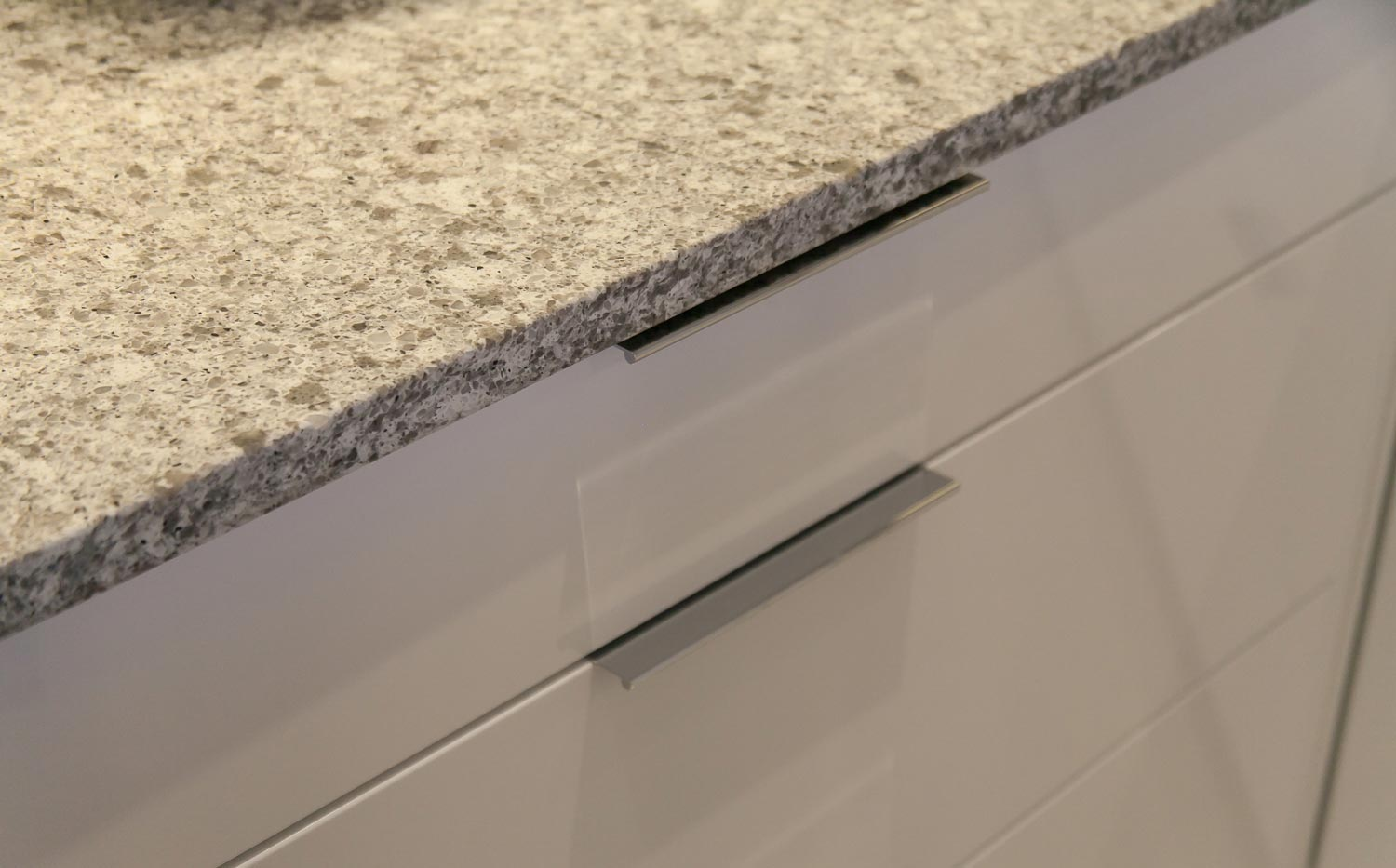 Granite countertops over gleaming white glass front cabinets