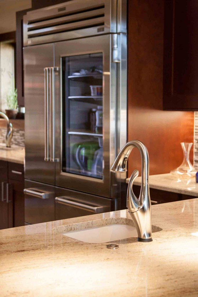 extra sink and faucet in the island plus views of glass front refrigerator