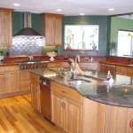 Green custom kitchen with Stainless steel stove hood and backsplash treatment