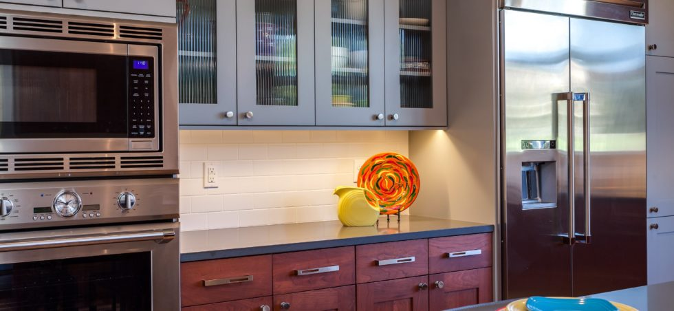 Stained wood cabinets paired with grey painted shaker style glass front cabinets