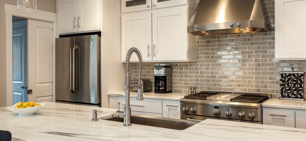White kitchen cabinets with granite island