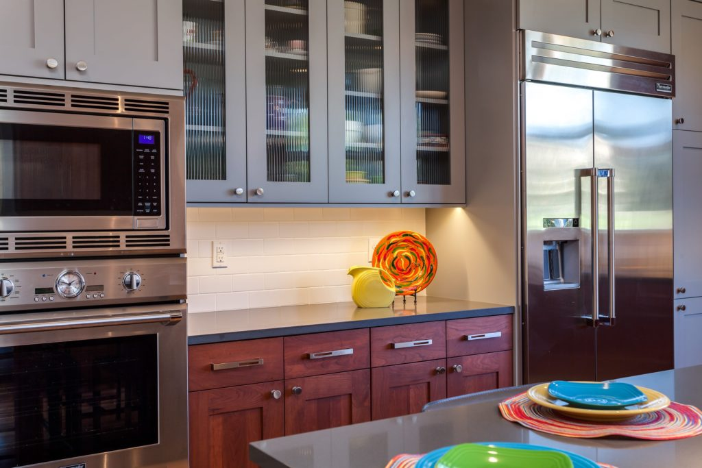 Natural wood cabinets paired with grey painted upper cupboards in this organized kitchen in Denver Colorado.