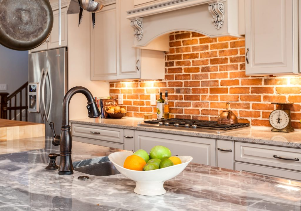 Kitchen with marble countertop island and brick backsplash