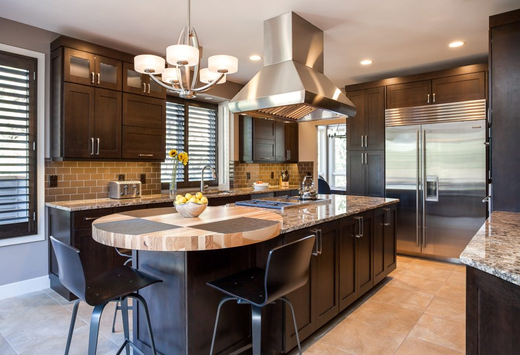 eat in kitchen island Dark wood cabinet kitchen with large stainless steel oven hood
