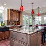 Natural wood cabinets with red glass lighting fixtures