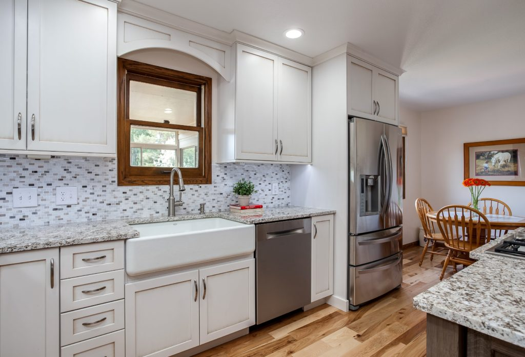 White painted cabinets with granite countertops and farmhouse or skirt sink