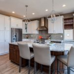 White painted kitchen cabinets with chandeliers over island