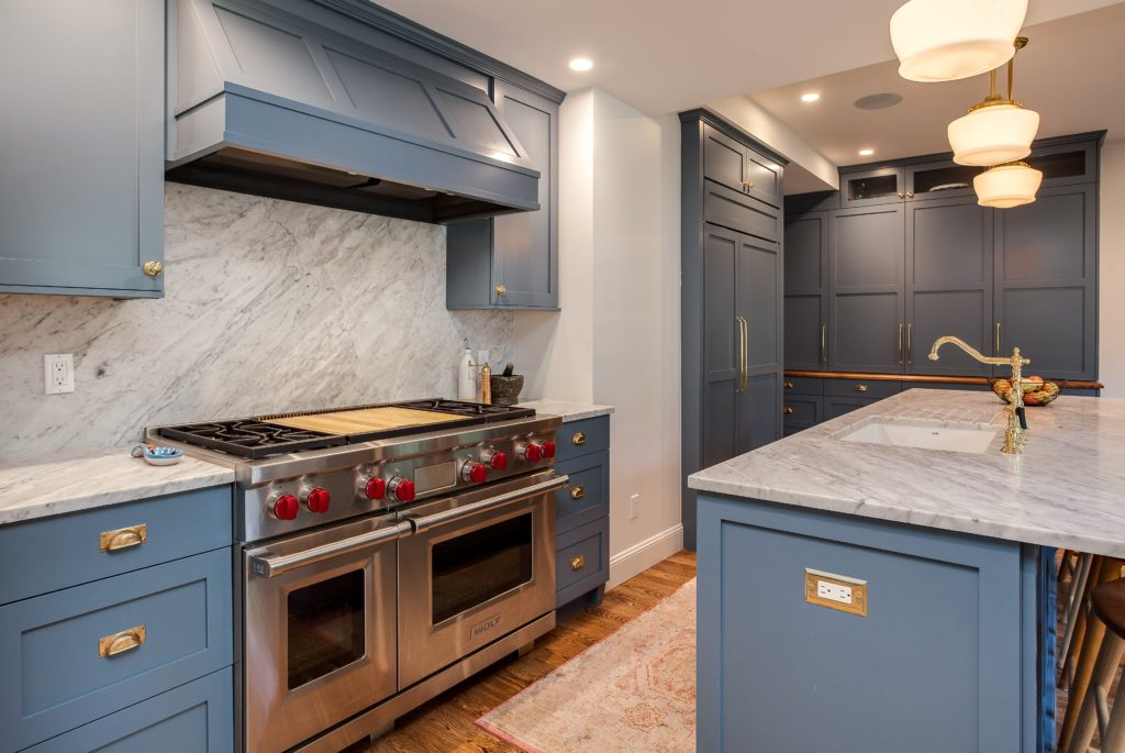 Custom painted blue cabinetry and stove hood with wolf double oven gas range