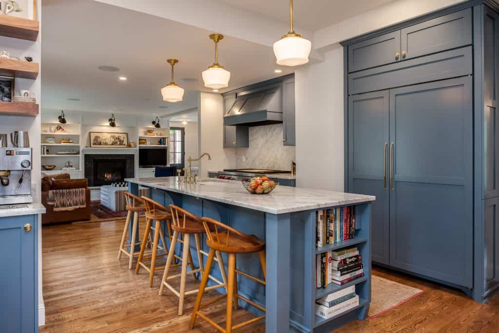 Muted blue painted cabinets with gold accents long island with sink and seating