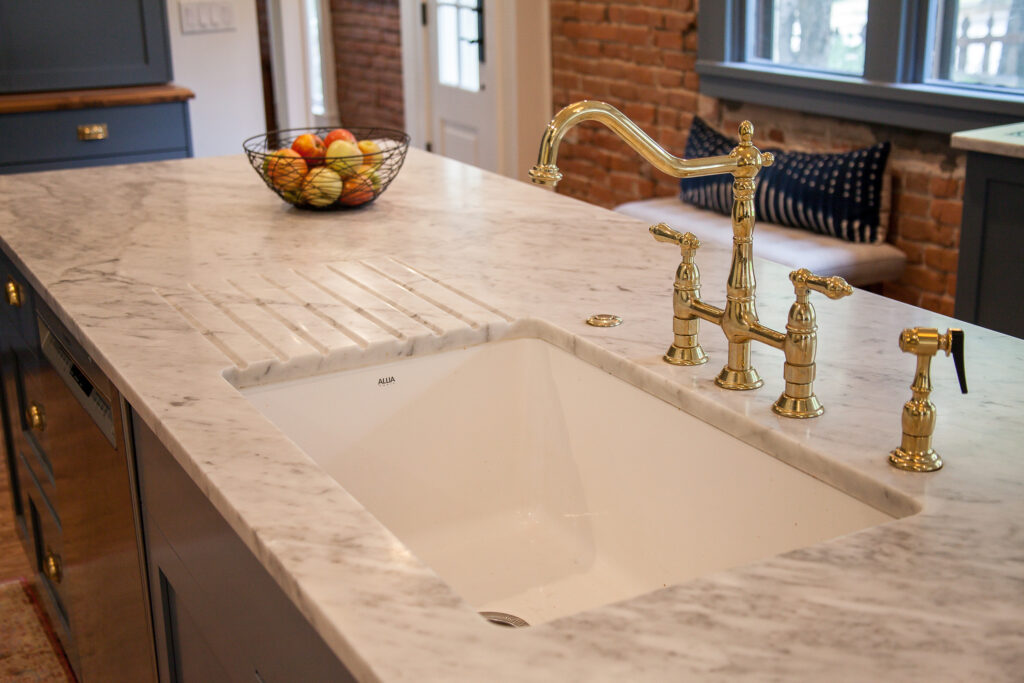 drainboard cut into the marble countertop at the sink for quick and easy cleanup