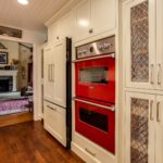 Red double ovens in this white painted kitchen remodel in Cherry Hills