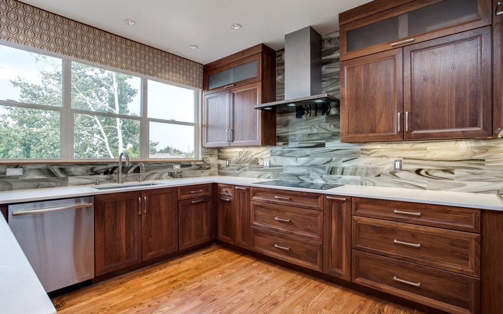 This is transitional Modern design. Shaker cabinets Stained glass backsplash Walnut wood cabinets White quartz counters