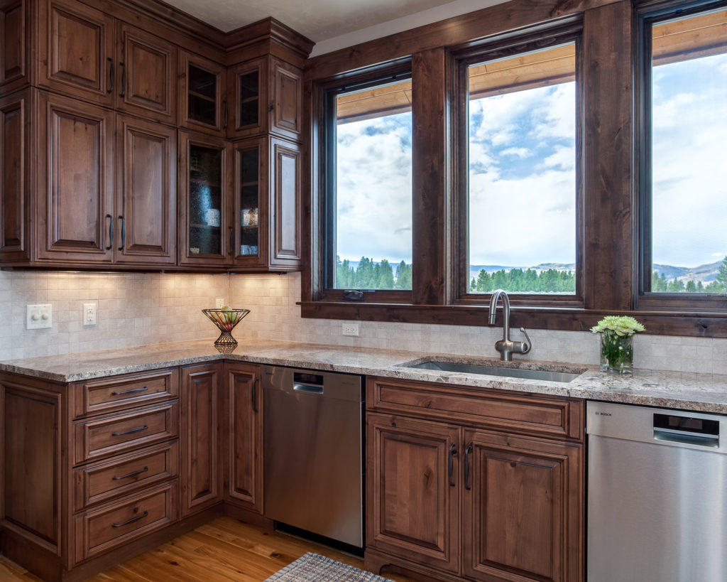 Mountain Home Kitchen with rustic alder wood cabinets frame windows of the views of Fraser valley colorado beyond