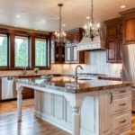 Natural wood cabinet kitchen with small chandeliers over island