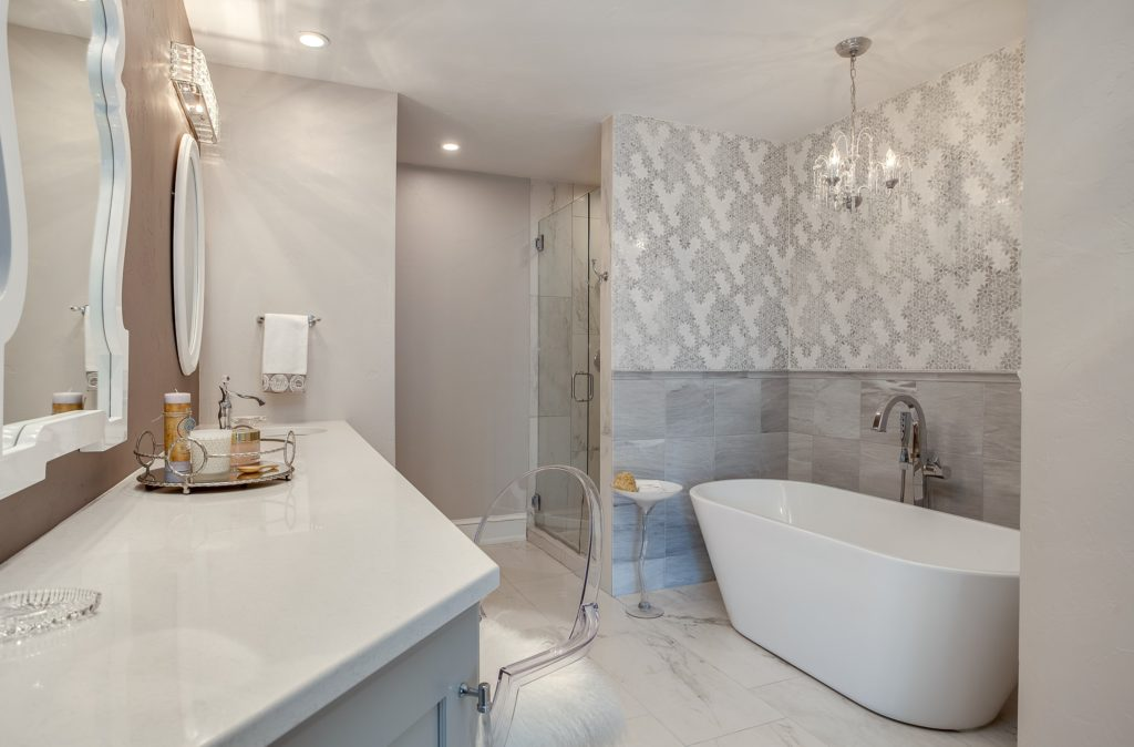 Light grey and white bathroom with soaking tub and chandelier
