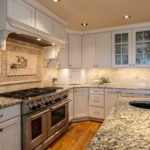 Shaker style kitchen cabinets with granite countertops and custom range hood
