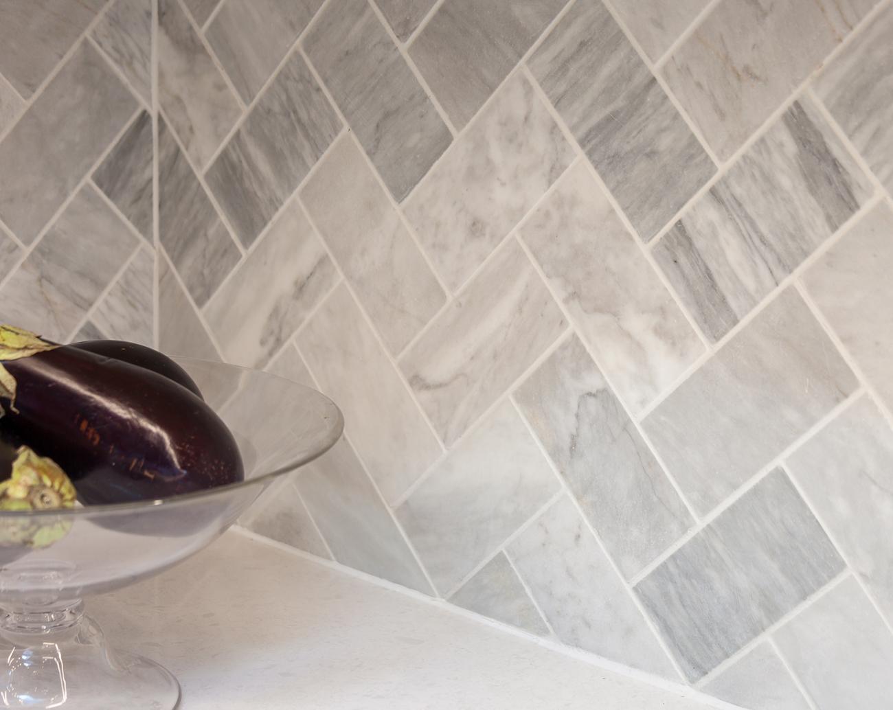 Bianco Venatino 3x6 Hone Carrera Marble, Installed in a Herringbone pattern