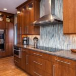 Natural wood cabinets with glass tile backsplash