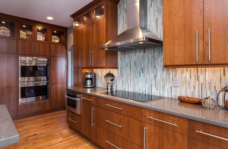 Natural wood cabinets with glass tile backsplash