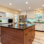 White kitchen cabinets with granite island