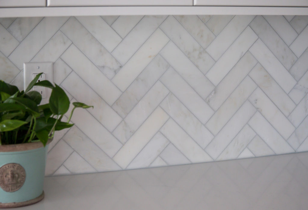 "The kitchen backsplash is Akdo ""Carrara Bella"" Marble field tile, polished, 2 x 8 tile installed in a herringbone pattern."
