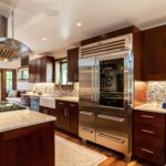Dark wood cabinet kitchen with large stainless steel refrigerator
