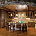 Amazing stone arch leading into natural wood kitchen