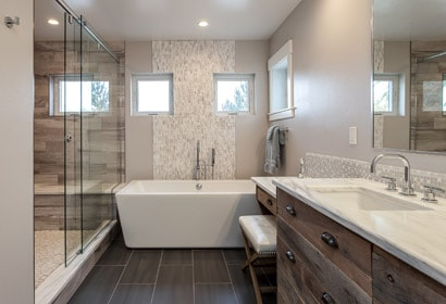 Freestanding tub in this masterbath remodel featuring barnwood cabinets
