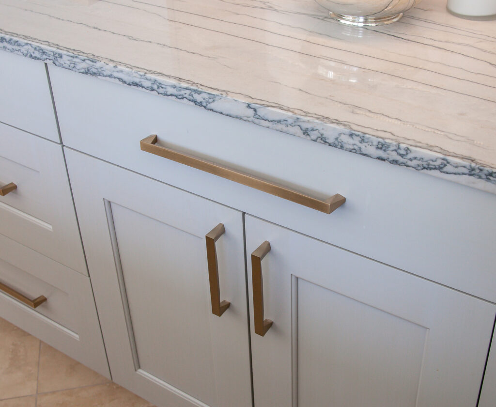 Brass hardware on grey transitional cabinets
