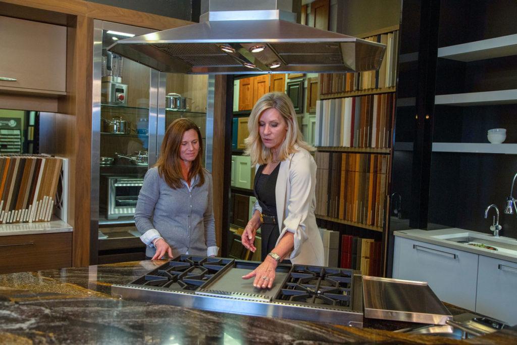 Juli walks a client through the Denver Colorado Showroom at JM Kitchen & Bath