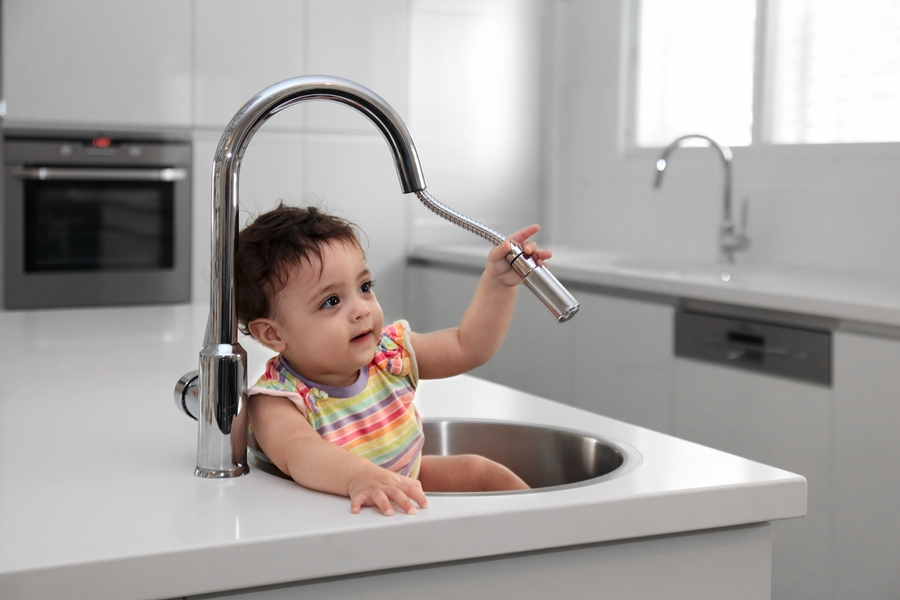 cute kid sitting in the kitchen sink