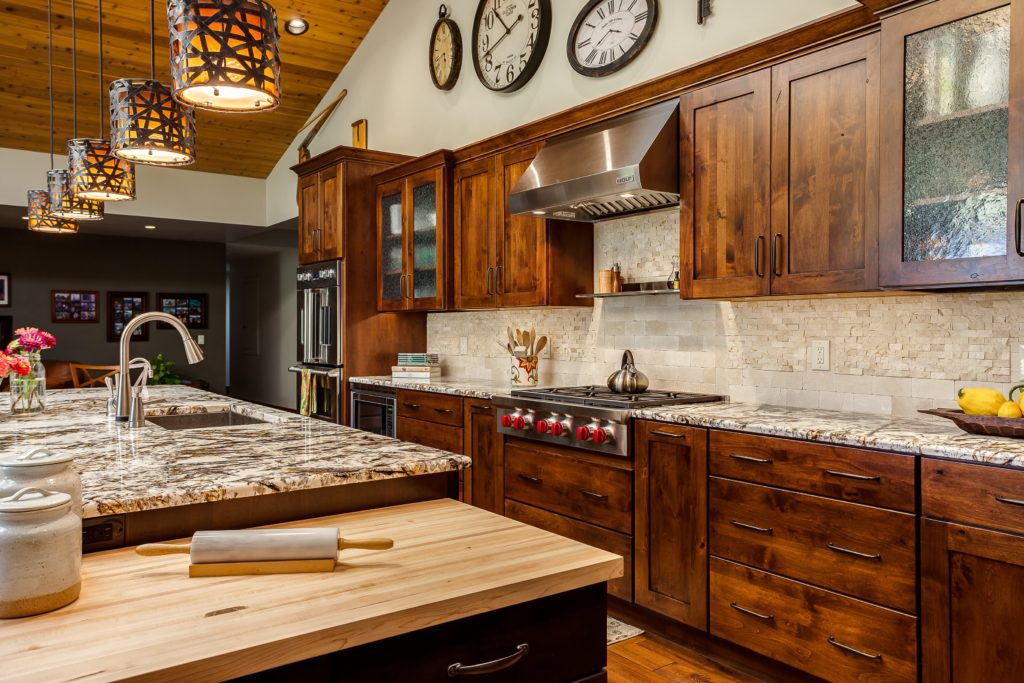 This kitchen remodeling project features Dark natural wood cabinets with rustic lighting features