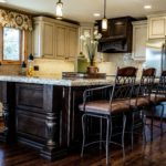 Off white painted cabinet kitchen paired with dark wood island in center
