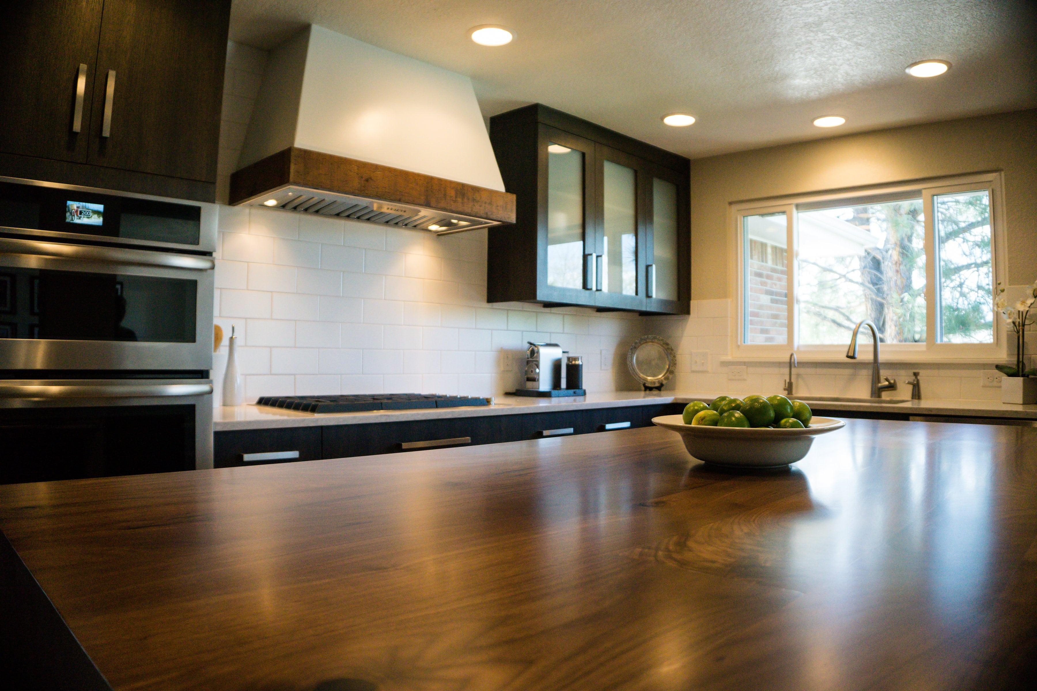 Large wood countertop island in dark wood kitchen with unique range hood