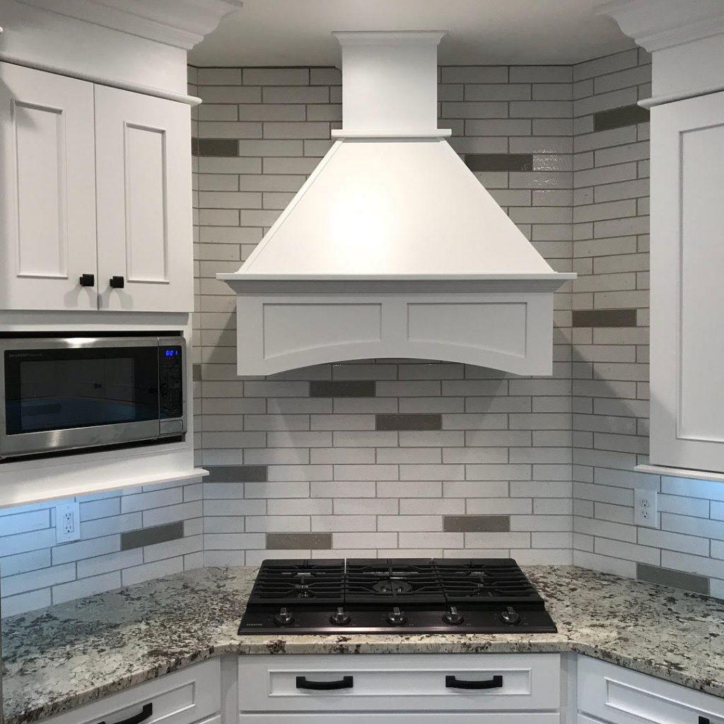 white stove hood with italian subway tile
