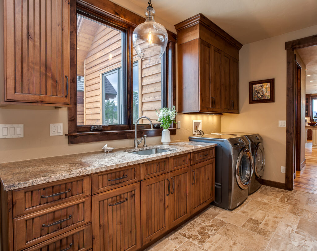 wood cabinets and utility sink in large laundry room